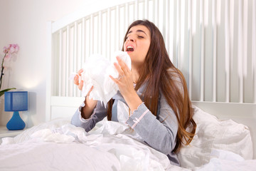 Woman in bed sneezing holding many handkerchief