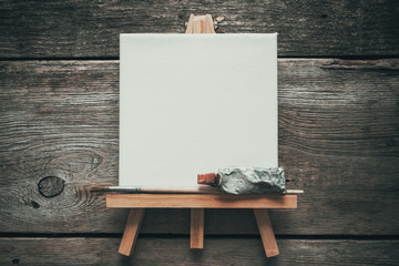 Canvas on easel, paint tube and paintbrush. Old wooden background. Top view. Flat lay. Copy space for text.