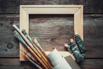 Wooden stretcher bar, paintbrushes, roll of artist canvas and paint tubes on old wooden background. Top view. Copy space for text.