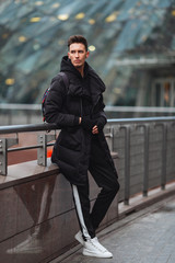 Fashionable man stand on the street near buildings. Winter, autumn outfit. Jacket with blouse and white sneakers.