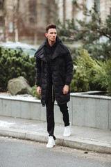 Stylish man wolk on the street. Winter cold outfit. Big jacket with white sneakers. Blured background street. Profecional model photo.