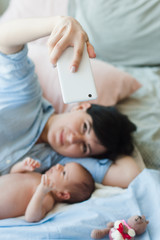 mother takes a selfie on smartphone with her child. adorable newborn baby. happy motherhood.