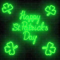 Neon glowing happy saint patricks day with clover leaves on a dark brick wall background.