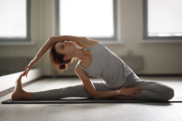 Young sporty woman doing yoga stretching exercise sitting in gym near bright windows
