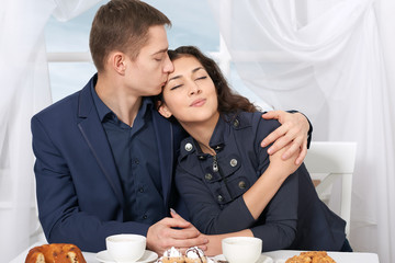 happy couple drinking coffee and resting near window with a sky view - travel and love concept