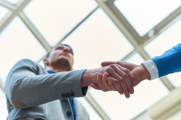 Low angle close up of two business people shaking hands against background of glass roof i modern office building, copy space