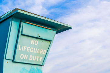 weathered sign saying 'No Lifeguard On Duty' on a lifeguard platform at a beach in Santa Barbara, California with copy space