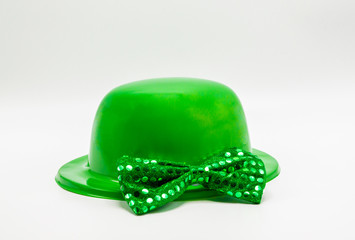 bright green derby hat and bow tie with sequins for St. Patrick's Day isolated on white
