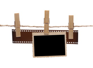 Blank instant photo and film strip hanging on clothesline. Isolated on white with clipping path