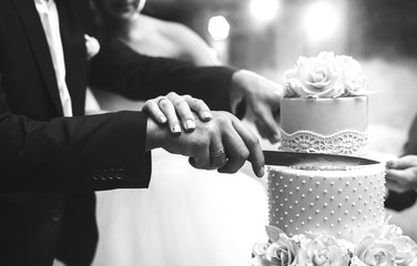 A bride and a groom is cutting their wedding cake. beautiful cake. nicel light. wedding concept. black and white photo