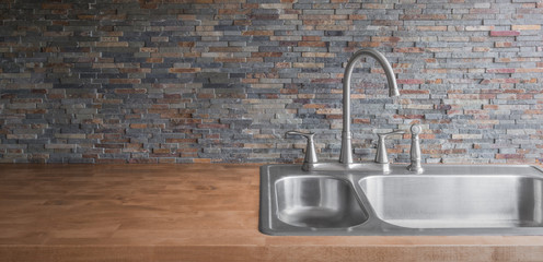 Wooden countertop with a modern stainless steel sink and faucet and a stone tile backsplash