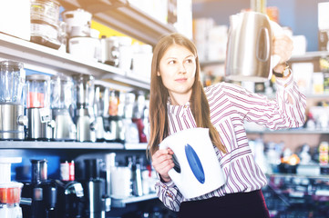 Young attractive woman choosing kettle in household appliances store