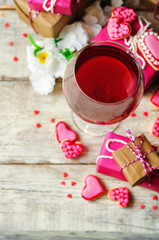 Glass of red wine with heart shape cookies, flowers and gifts