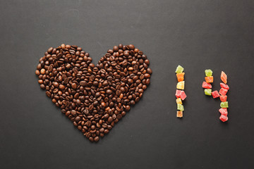 Brown coffee beans in form of heart isolated on black texture background for design. Saint Valentine's Day card on fabruary 14, holiday concept. Number 14 of colored square candied fruits or peel.