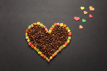 Colorful paper, candied fruits in the form of heart, brown coffee beans isolated on black background for design. Saint Valentine's Day card, fabruary 14, holiday concept. Copy space for advertisement.