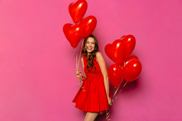 Smiling girl holding air balloons in two hands, posing at camera. St. Valentine's day. Dressed in red dress, on pink background.