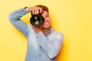 Cheerful young man with professional camera, taking a photo. On yellow background. Dressed in jeans shirt.