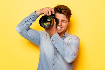 Handsome young photographer with professional camera, taking a photo. On yellow background. Dressed in jeans shirt.