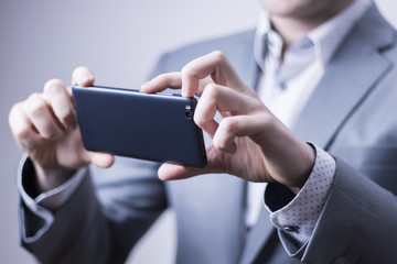 Closeup of a businessman in grey suit taking picture with a mobile phone