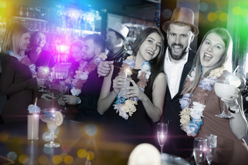 Man with female friends on Hawaiian party in bar