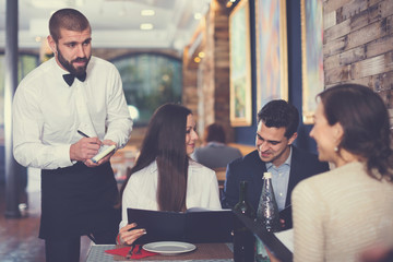 Waiter with notebook taking order from friendly company indoors