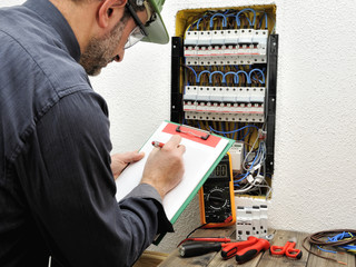 Electrician technician at work with protective helmet on a residential electric panel
