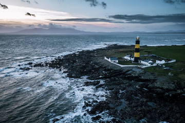 Aerial of the atlantic coast and black and blue lighthouse in Ireland near the ocean and sunset