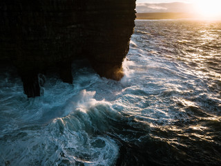 Waves crashing against Downpatrick Head sea stack standing in the atlantic ocean in Ireland during sunset