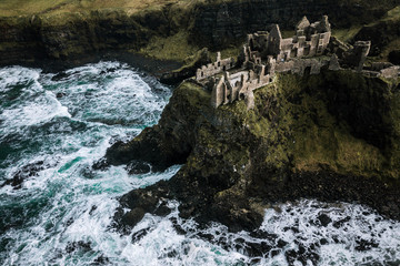 Dunluce Castle  standing atop a cliff in the atlantic ocean in Ireland during sunset