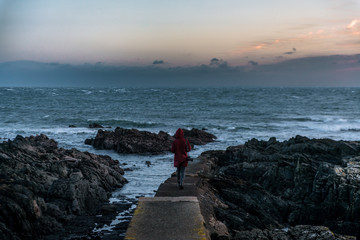 Young adult woman standing on a stone pier at the atlantic coast near a lighthouse in Ireland and watching the ocean and sunset