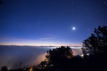 Night Sky and the Moon Above Foggy Landscape