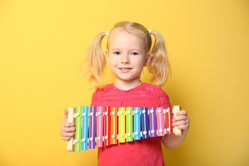 Cute little girl with xylophone on color background