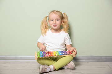Cute little girl playing with xylophone near color wall