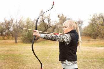 Attractive woman practicing archery outdoors