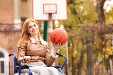 Young woman in wheelchair with ball on playground