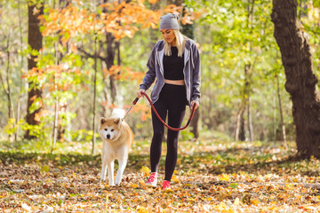 Girl and her dog walking in park