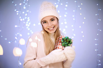 Happy woman with gift box against blurred lights