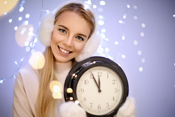 Happy woman with clock against blurred lights