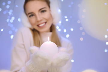 Happy woman with candle against blurred lights