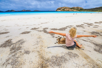 Happy caucasian woman with open arms near a Kangaroo lying at Lucky Bay in Cape The Grand National Park, Esperance, Western Australia. Female tourist enjoys one of the WA's most famous beaches.