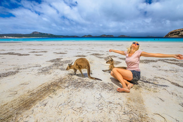 Happy caucasian woman with open arms near a two Kangaroos at Lucky Bay in Cape The Grand National Park, Esperance, Western Australia. Female tourist enjoys one of the WA's most famous beaches.