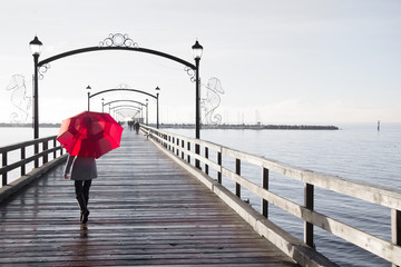 Woman holding a red umbrella walking on a rainy day on the pier in White Rock, British Columbia, Canada.