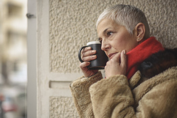 Sad senior elderly lady drinking coffee, thinking about some distant memories Wall mural