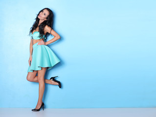 Simply beautiful and smiling woman on blue background.