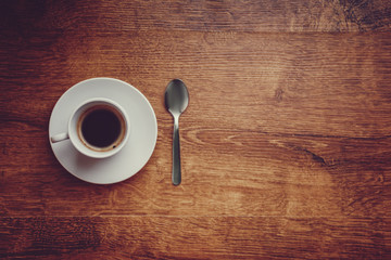 top view of white Cup with black coffee on a white saucer and teaspoon on dark brown wooden background