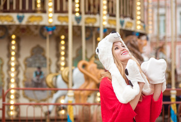 Expressive blonde woman wearing red knitted sweater and funny hat, posing at the background of carousel with lights