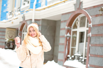 Positive young girl dressed in winter trendy apparel and drinking coffee at the street