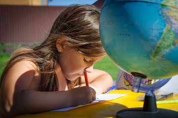 Little girl draws markers outdoors in summer