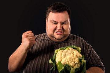 Diet fat man eating healthy food . Healthy breakfast with vegetables cauliflower for overweight person. Man is angry with low quality meal of product.
