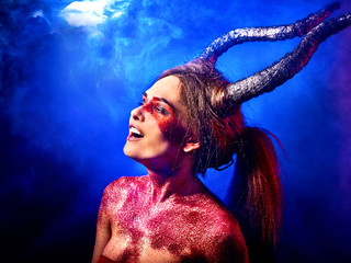Mad satan woman on black magic ritual of in hell. Witch reincarnation mythical creature on Sabbath. Happy devil on Halloween. Capricorn zodiac astrology. Make-up for night club.